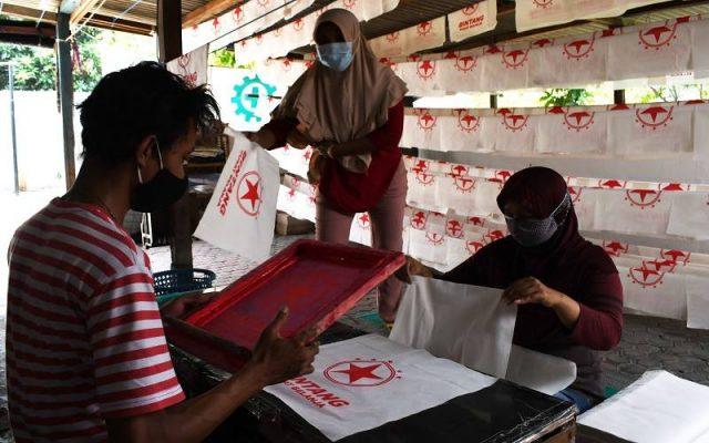 Pekerja membuat tas berbahan kain di tempat Usaha Mikro Kecil Menengah (UMKM) di Kota Madiun, Jawa Timur, Sabtu (31/7/2021). Perajin UMKM tersebut tetap bertahan untuk berproduksi meskipun saat PPKM permintaan turun dari sebelum pandemi 20.000 buah per bulan menjadi 2.000 buah per bulan dengan harga Rp9 ribu hingga Rp18 ribu per buah. ANTARA FOTO - Siswowidodo